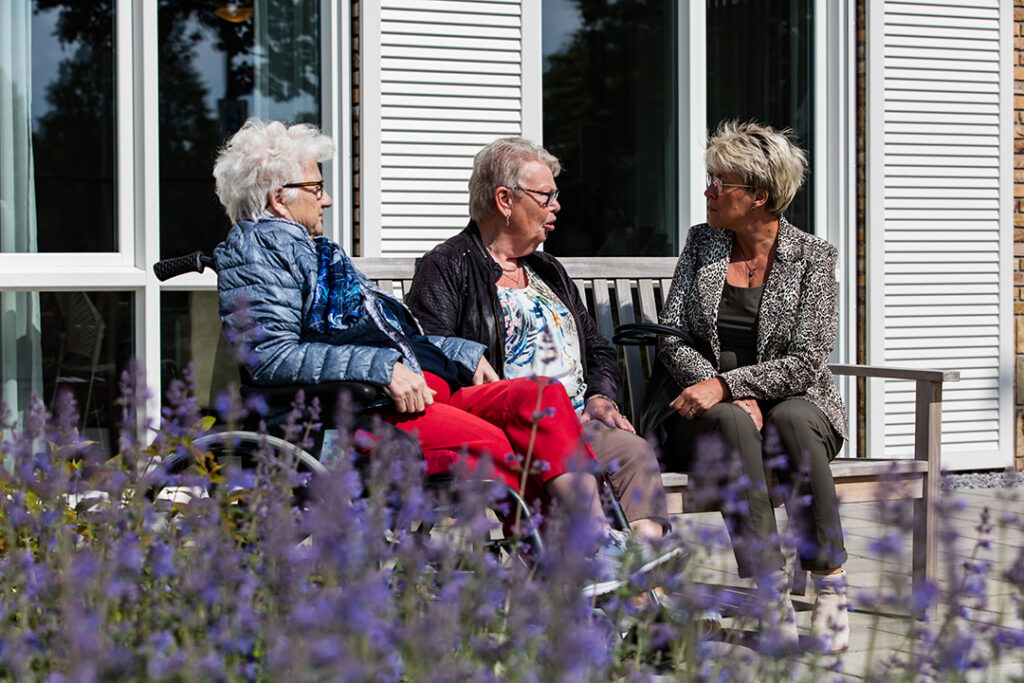 Dinie van Lenthe en haar moeder kletsen samen met een andere bewoonster van Het Vechtdalhuis in Hardenberg buiten op een bankje.