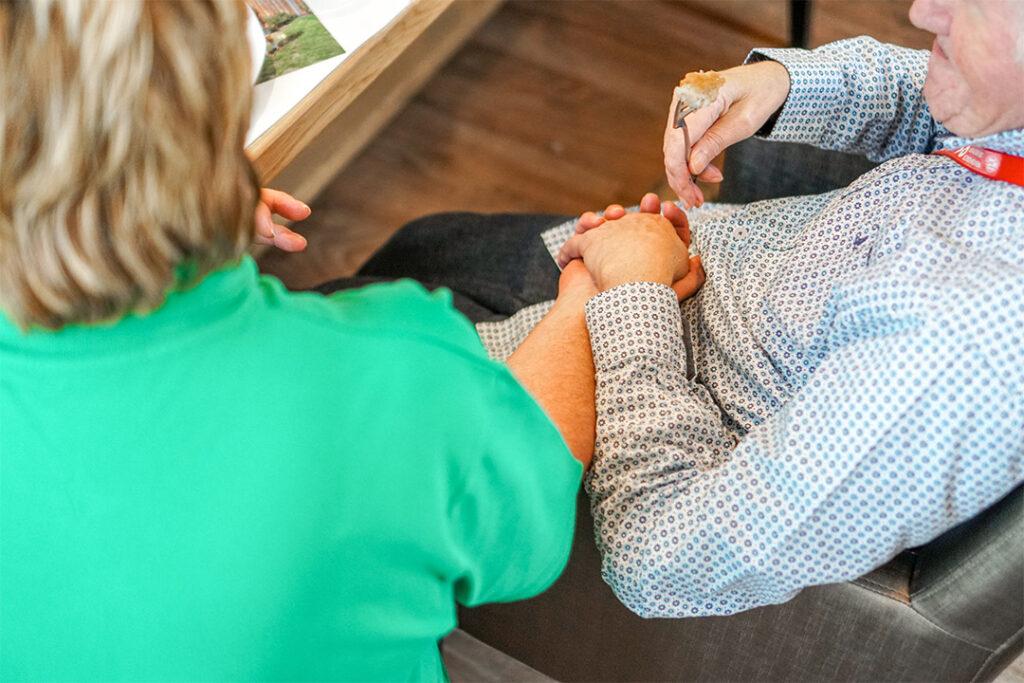 Een medewerker houdt de hand vast van een bewoner met dementie. Lichamelijk contact werkt als behandeling tegen onrust.