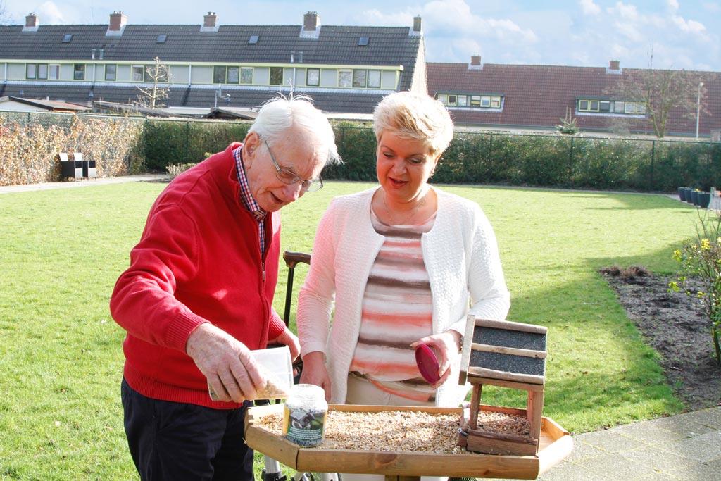Carmen Willemsen samen met haar vader met dementie in Het Wilderinkhuis in Hengelo waar ze de vogeltjes gaan voeren in de grote tuin.