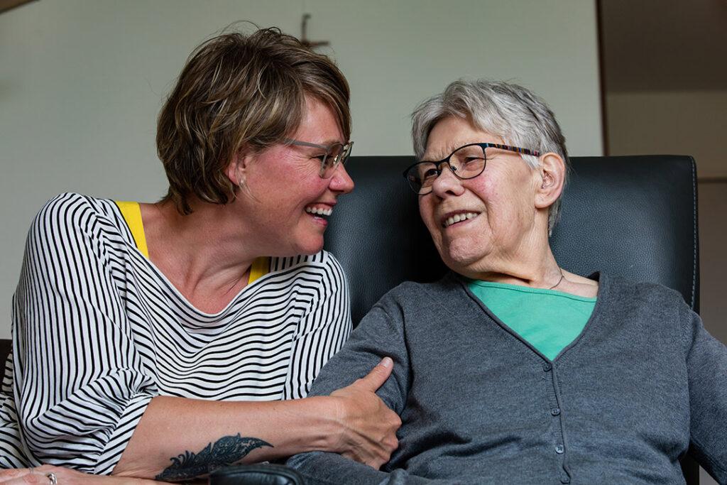 Hetty en haar moeder met dementie knuffelen op de bank bij Dagelijks Leven