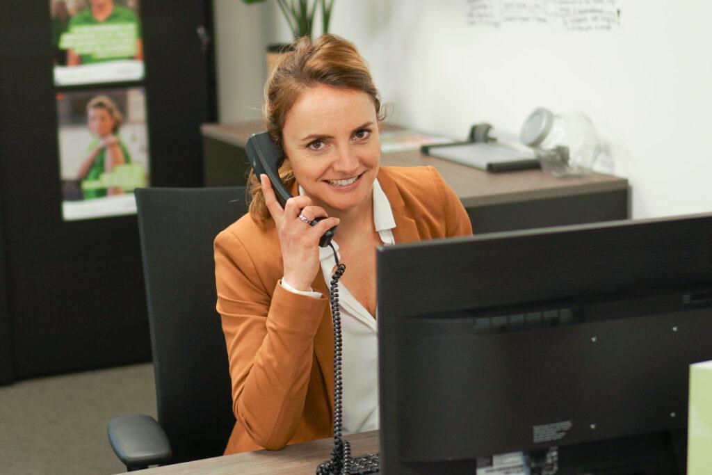 Een medewerker van het secretariaat lacht naar de camera en helpt u graag met al uw vragen over Dagelijks Leven
