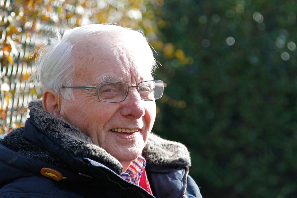Meneer Willemsen zit buiten te genieten van de zon in Het Wilderinkhuis in Hengelo