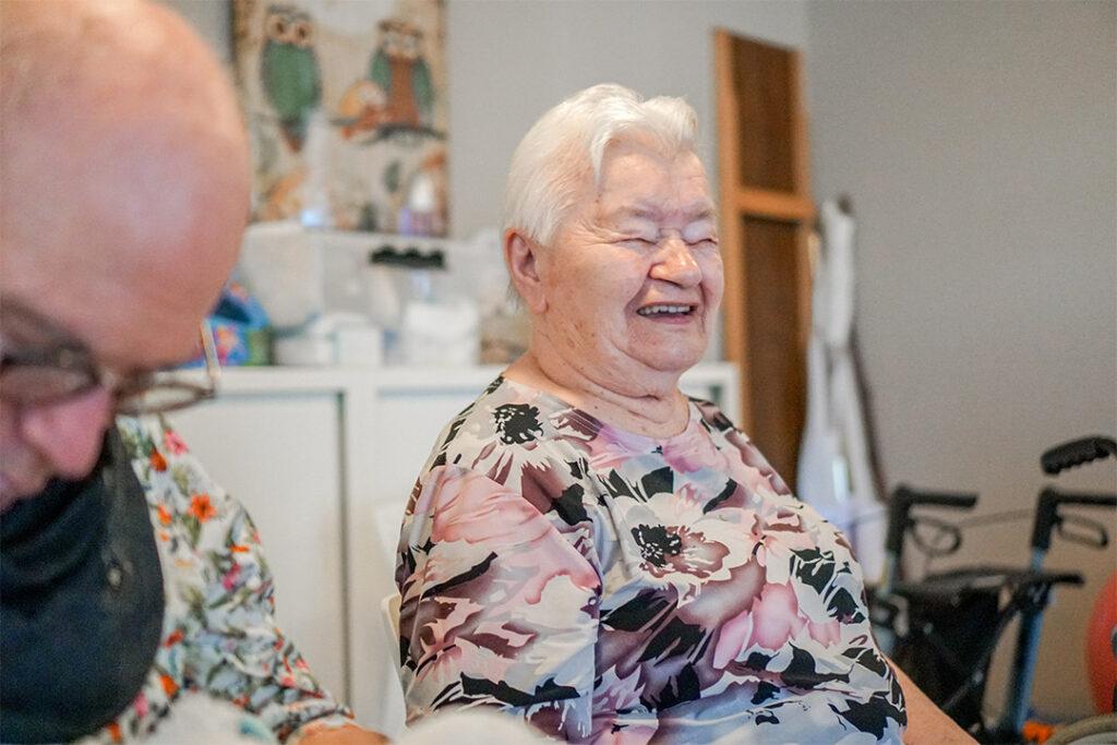 Een mevrouw die woont bij dagelijks leven lacht tevreden