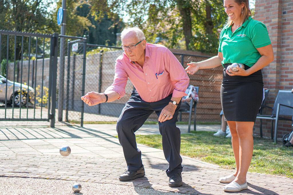 Een bewoner speelt jeu de boules op het terrein van een Dagelijks Leven locatie
