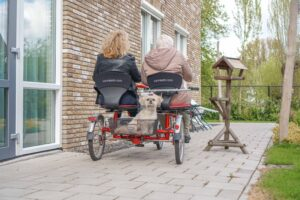 Foto genomen terwijl moeder en dochter samen wegfietsen met het hondje achterop.
