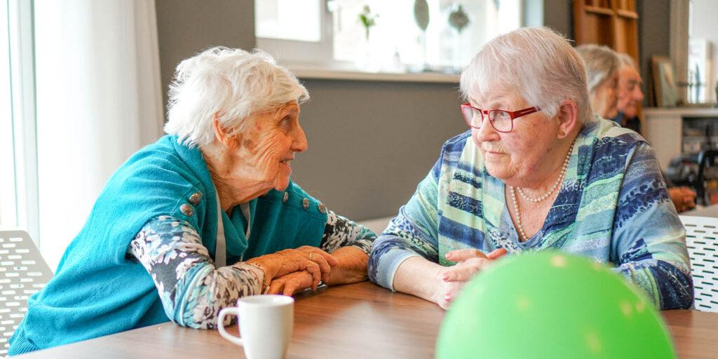 Twee bewoonster zitten aan tafel tijdens een activiteit te praten over wanneer zij zich hebben ingeschreven