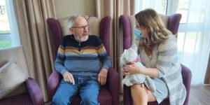 Verzorgende IG Isabel zit naast een bewoner van Dagelijks Leven in een fauteuil. Ze laat hem een knuffelhond zien.
