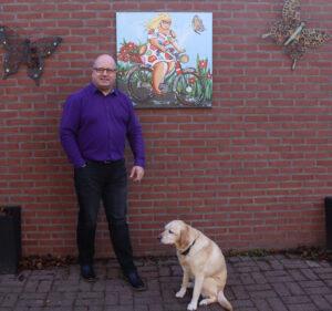 Blogger Pieter Jansen, GVP in opleiding, staat samen met zijn hond buiten voor een muur met schilderij
