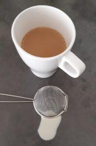 Een kopje koffie met een zeefje en druppels melk ernaast.