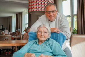 Bewoonster Abtswoudehuis zit in een rolstoel in de huiskamer van Dagelijks Leven, haar zoon staat achter haar en leunt op de stoel. Ze lachen naar de camera.