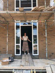 Locatiemanager van Het Blaauwhofhuis in Joure in de deuropening van de kleinschalige woonzorglocatie voor mensen met dementie