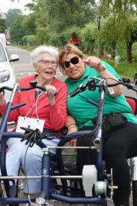 Een bewoner met dementie samen met een zorgmedewerkerp op de duofiets tijdens een sponsortocht bij Dagelijks Leven.