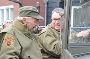 Bewoner met dementie zit samen met zoon in een legervoertuig.